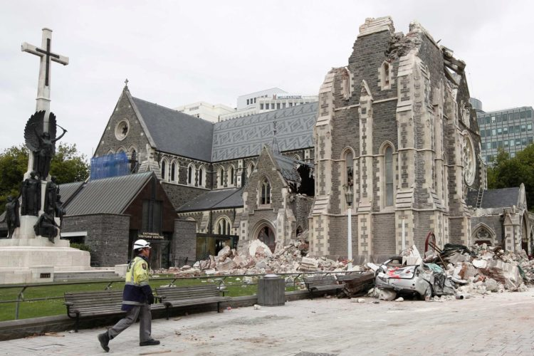 FILE - In this Feb. 26, 2011, file photo, a relief worker walks past the earthquake-damaged ChristChurch Cathedral in Christchurch, New Zealand. Five years after the devastating earthquake, the ravaged city center is still largely an empty core, and it's unclear how long it will remain that way. The ChristChurch Cathedral, the city's best-known building, has come to symbolize the quagmire. The Anglican church decided it was too badly damaged to rebuild and began demolishing it. But that work was stopped after preservationists took legal action, leaving the building's fate in limbo. (AP Photo/Mark Baker, File)