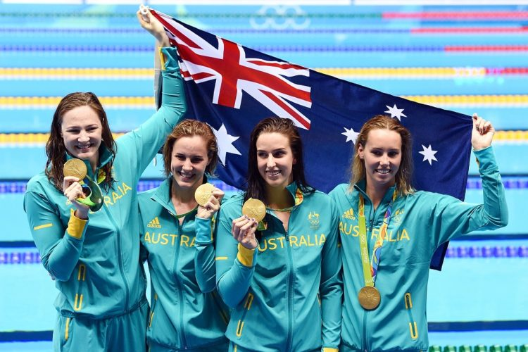 Australian relay swimmers Cate Campbell, Bronte Campbell Emma McKeon, and Brittany Elmslie celebrate their gold medal win in the Womens 4x100 Freestyle Relay, at the Olympic Aquatics Stadium on day one, of the Rio 2016 Olympic Games in Brazil, Saturday, AUG. 6, 2016. (AAP Image/Dean Lewins) NO ARCHIVING, EDITORIAL USE ONLY